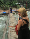 Beautiful girl is looking back with fright. Bukit Lawang, Indonesia - April 15, 2015: beautiful girl is looking back with fright on the bridge in Bukit Lawang Royalty Free Stock Photo