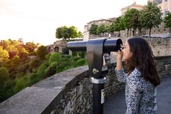 Beautiful girl looking at Bergamo lower city through touristic telescope at sunset Royalty Free Stock Photos