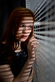 Beautiful girl looking through the blinds. Close-up Royalty Free Stock Image