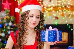 Beautiful girl looking at Christmas gift Stock Photos