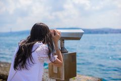 Beautiful girl looking at coin operated binocular Stock Images