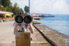 Beautiful girl looking at coin operated binocular Stock Photography