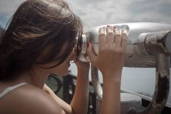 Beautiful girl looking at coin operated binocular Royalty Free Stock Photography