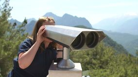 Beautiful girl is looking at coin operated binoculars at the top of mountain. Young woman looking through coin operated binoculars at beautiful view of stock footage