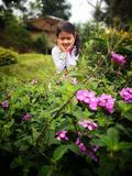 Beautiful girl looking happy sorrounded by flower stock photos