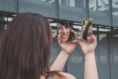 Beautiful girl looking at herself in a broken mirror Royalty Free Stock Photography
