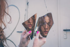 Beautiful girl looking at herself in a mirror Stock Images