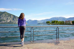 Beautiful girl looking lake and mountains sunny landscape on background outdoor. Travel healthy lifestyle concept. Royalty Free Stock Photo