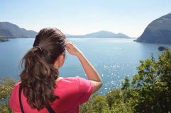 Beautiful girl looking lake and mountains sunny landscape on background outdoor. Travel healthy lifestyle concept. Stock Images