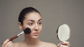 Beautiful girl looking in the mirror and applying cosmetic with a big brush. Royalty Free Stock Photography