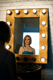 Beautiful girl looking through the mirror in dressing room Royalty Free Stock Photography