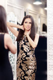 Beautiful Girl Looking in the Mirror and Trying on an Elegant Dress Royalty Free Stock Photography