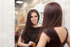 Beautiful Girl Looking in the Mirror and Trying on an Elegant Dress Stock Images