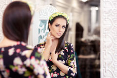 Beautiful Girl Looking in the Mirror and Trying on Floral Dress Stock Photography