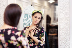 Beautiful Girl Looking in the Mirror and Trying on Floral Dress Royalty Free Stock Photo