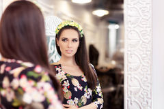 Beautiful Girl Looking in the Mirror and Trying on Floral Dress Royalty Free Stock Images