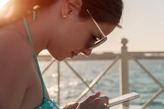 Beautiful girl looking at the phone at the sea wearing sunglasses, in a bathing suit, background of sea blue water Royalty Free Stock Photos