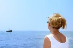 Beautiful girl looking the sea. On beach under blue sky Royalty Free Stock Photos