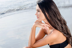 Beautiful girl looking at the sea waiting. Attractive young woman with long brunette hair looking at the sea. Girl wearing a strapless top, romantic look Royalty Free Stock Photos