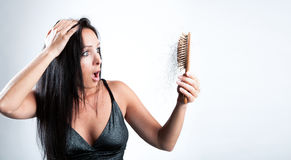 Beautiful girl is looking shocked to her hair brush.  Stock Photo