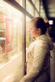 Beautiful girl looking in the shopwindow on the night. Royalty Free Stock Images