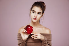 Beautiful girl looking in side holding red apple over pink background. Copy space. stock photos
