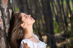 Beautiful girl looking up with eyes closed in the woods Stock Images