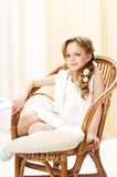 Beautiful girl looking at you. Cute little girl relaxing in wooden chair Royalty Free Stock Photos