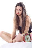 Bored girl looks at alarm clock blowing Stock Photos