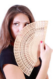 Beautiful girl looks away and hides her mouth and nose by fan Royalty Free Stock Image
