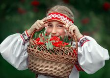 A beautiful girl looks through a basket with Rowan berries in her hands and smiles