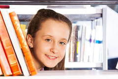 Beautiful girl looks through bookshelf portrait Stock Photos