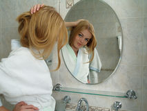 The beautiful girl looks in a mirror in a bathroom Stock Image