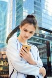 Beautiful girl looks in a mobile phone. royalty free stock images