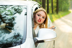 Beautiful girl looks out the car window and strongly swears Royalty Free Stock Images