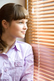 Beautiful Girl Looks Out Of The Window Royalty Free Stock Photos
