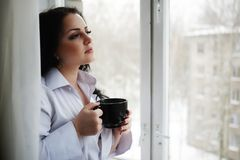 Beautiful girl looks out of window and holds a cup. Winter morning. Stock Photo