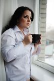 Beautiful girl looks out of window and holds a cup. Winter morning. Royalty Free Stock Photography