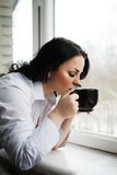 Beautiful girl looks out of window and holds a cup. Winter morning. Stock Image