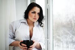 Beautiful girl looks out of window and holds a cup. Winter morning. Royalty Free Stock Photos