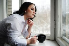 Beautiful girl looks out of window and holds a cup. Winter morning. Stock Photos
