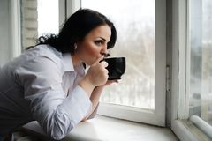 Beautiful girl looks out of window and holds a cup. Winter morning. Royalty Free Stock Photo