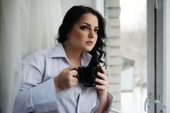 Beautiful girl looks out of window and holds a cup. Winter morning. Stock Photography