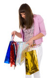 Beautiful girl looks in a package with purchases Royalty Free Stock Image