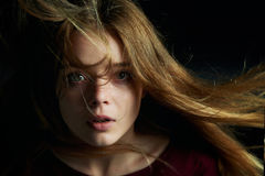 Beautiful girl looks piercing eyes into the camera. Hair flying. Drama. Studio photography in low key on a dark Royalty Free Stock Photo