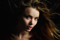 Beautiful girl looks piercing eyes into the camera. Hair flying. Drama. Studio photography in low key on a dark Royalty Free Stock Image