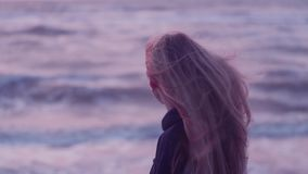 Beautiful girl looks towards the sea and turns camera, her hair develops, wind, waves against the backdrop stock video