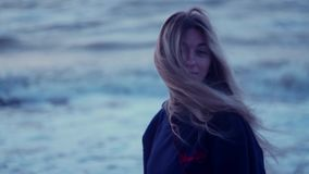 Beautiful girl looks towards the sea and turns to camera, her hair develops, wind, waves against the backdrop stock footage
