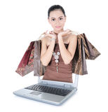 Beautiful girl with lots of shopping bags out of the laptop Stock Photography