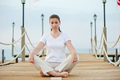 Beautiful  girl in lotus position resting on the pier at the sea Royalty Free Stock Photos